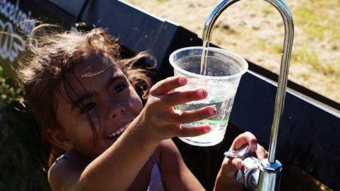 Child enjoying the sight of fresh water -  Walhallow, Australia